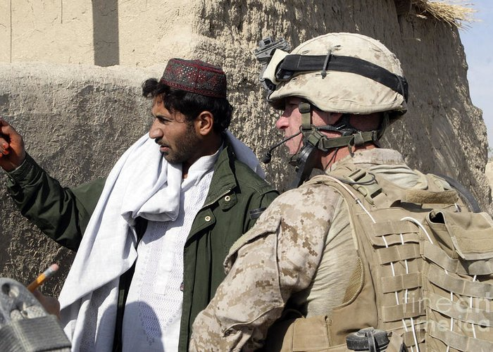 Marines Greeting Card featuring the photograph A Soldier Talks To A Local Villager by Stocktrek Images