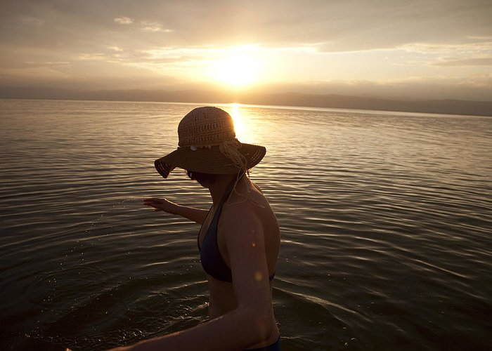 Color Image Greeting Card featuring the photograph A Woman Wades Into The Dead Sea by Taylor S. Kennedy