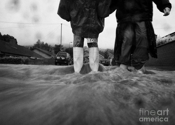 Rain Greeting Card featuring the photograph Children Walking In Heavy Rain Storm In The Street by Joe Fox