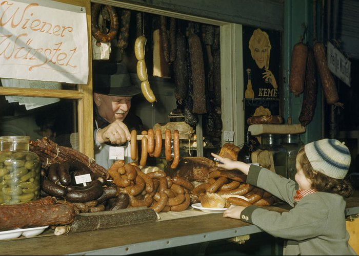 Outdoors Greeting Card featuring the photograph Vendor Holds Up Sausages For Young Girl by Volkmar Wentzel