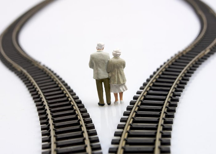 Contemplates Greeting Card featuring the photograph Figurines Between Two Tracks Leading Into Different Directions Symbolic Image For Making Decisions. by Bernard Jaubert