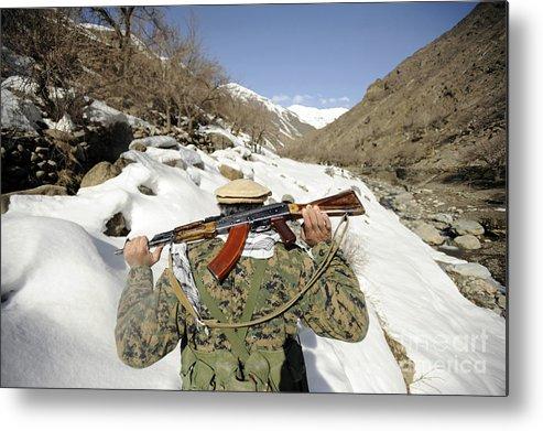 Terrain Metal Print featuring the photograph A Mujahadeen Guard Walks With U.s by Stocktrek Images