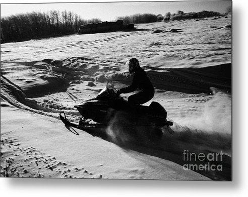 Man Metal Print featuring the photograph man on snowmobile crossing frozen fields in rural Forget Saskatchewan by Joe Fox