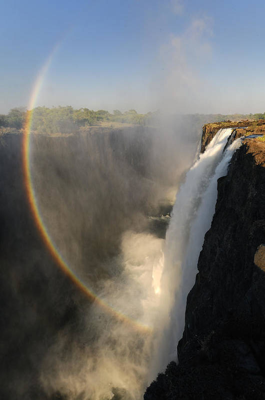 Rainbow At The Victoria Falls Poster featuring the photograph Victoria Falls by Christian Heeb