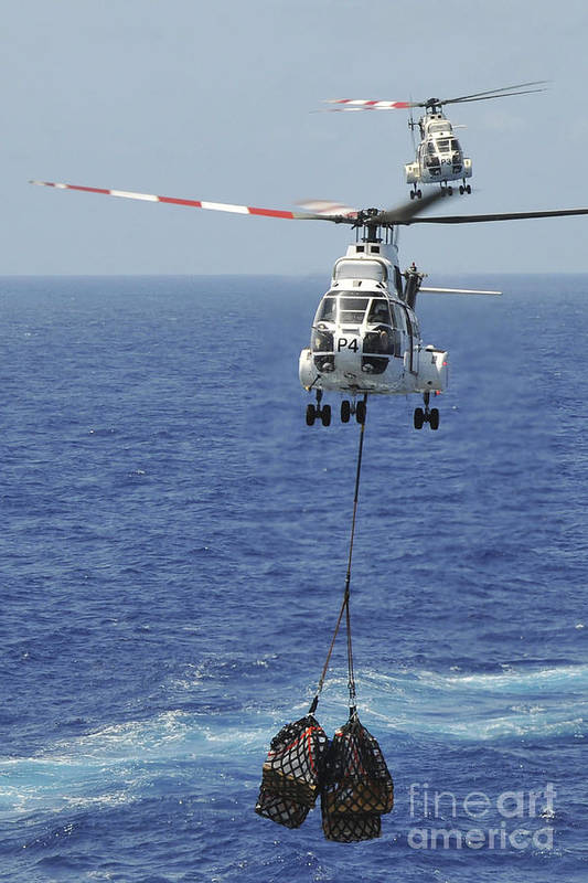 Replenishment At Sea Poster featuring the photograph Two Sa-330 Puma Helicopters Deliver by Stocktrek Images