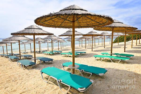 Beach Poster featuring the photograph Beach Umbrellas On Sandy Seashore by Elena Elisseeva