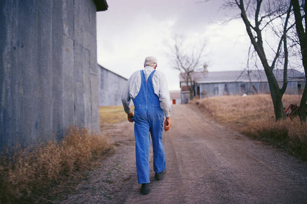 Scenes And Views Poster featuring the photograph An Elderly Farmer In Overalls Walks by Joel Sartore