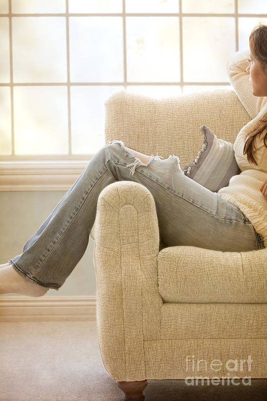 Woman; Lady; Female; Caucasian; Casual; Comfort; Comfortable; Lazy; Jeans; Socks; Sweater; Rips; Torn; Ripped; Hole; Chair; Sitting; Lounge; Lounging; Living Room; Indoors; Inside; Window; Wall; Carpet; Carpeting; Brunette; Crisp; Clean; Uncluttered; Sparse; Minimal; Alone; In Thought; Warm; Warmth Poster featuring the photograph Relaxed by Margie Hurwich