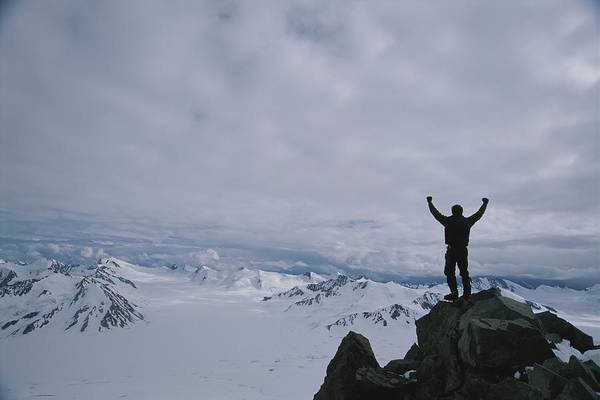Glaciers Poster featuring the photograph A Climber Raises His Arms In Triumph by John Burcham