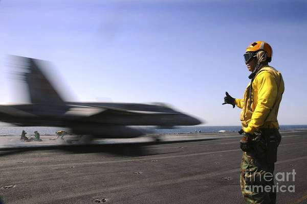 Uss Enterprise Poster featuring the photograph A Sailor Ensures An Fa-18c Hornet by Stocktrek Images