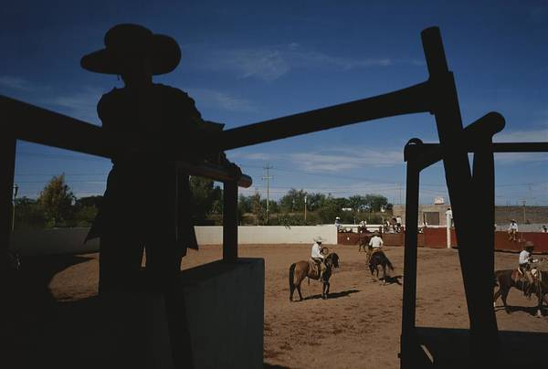 Cowboys And Cowgirls Poster featuring the photograph A Silhouetted Cowboy Watches Riders by Raul Touzon