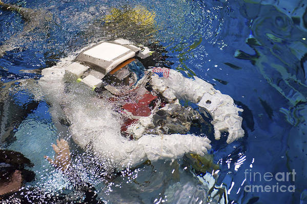 Underwater Poster featuring the photograph An Astronaut Is Submerged In The Water by Stocktrek Images