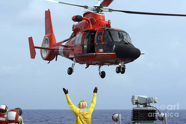 Helicopter Poster featuring the photograph Boatswain Mate Directs A Hh-65a Dolphin by Stocktrek Images