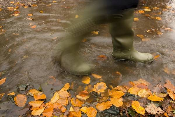 Boots Poster featuring the photograph Person In Motion Walks Through Puddle by John Short