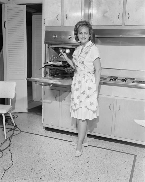 35-39 Years Poster featuring the photograph Portrait Of Woman Cooking In Kitchen by George Marks