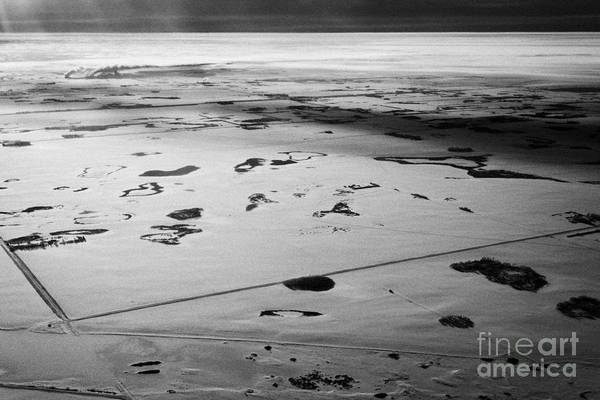 Aerial Print featuring the photograph aerial view of snow covered prairies and remote isolated farmland in Saskatchewan Canada by Joe Fox