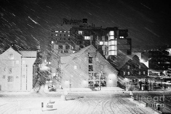 Looking Print featuring the photograph looking out atTromso bryggen quay harbour on a cold snowy winter night troms Norway europe by Joe Fox