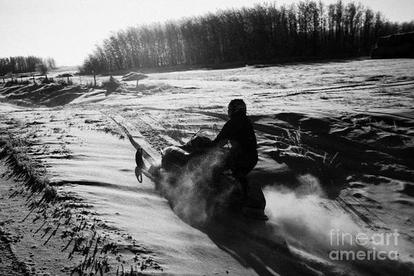 Man Print featuring the photograph man on snowmobile crossing frozen fields in rural Forget canada by Joe Fox