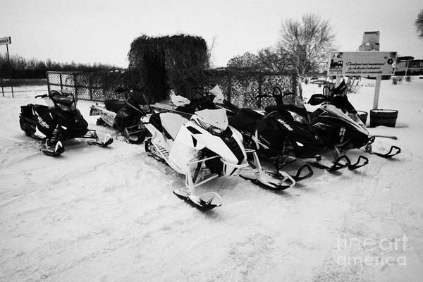 Snowmobile Print featuring the photograph snowmobiles parked in Kamsack Saskatchewan Canada by Joe Fox