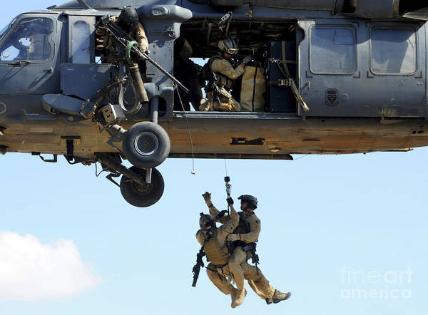 Csar Print featuring the photograph Pararescuemen Are Hoisted Into An Hh-60 by Stocktrek Images