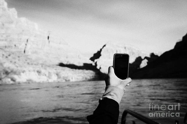 Man Print featuring the photograph man taking photos with smartphone during boat ride along the colorado river in the grand canyon Ariz by Joe Fox