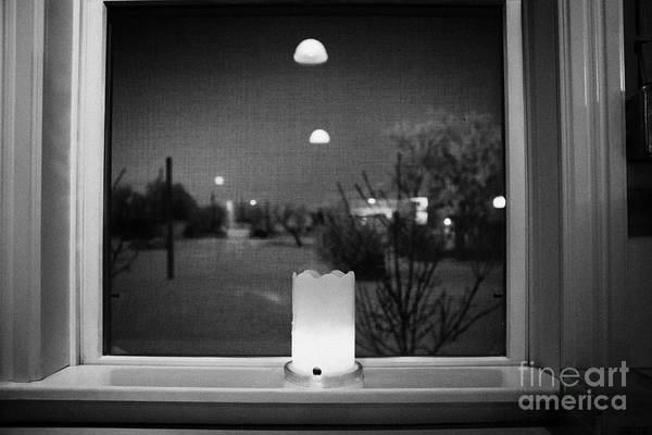 Looking Print featuring the photograph candle in the window looking out over snow covered scene in small rural village of Forget Saskatchew by Joe Fox