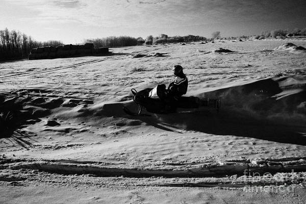 Man Print featuring the photograph man on snowmobile crossing frozen fields in rural Forget Saskatchewan Canada by Joe Fox