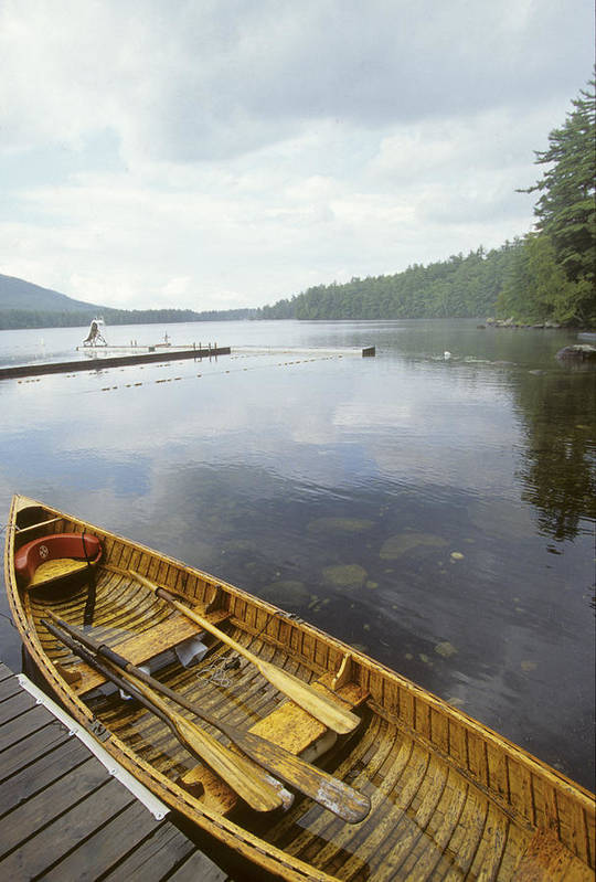 No People Print featuring the photograph A Canoe Floats Next To A Dock by Skip Brown