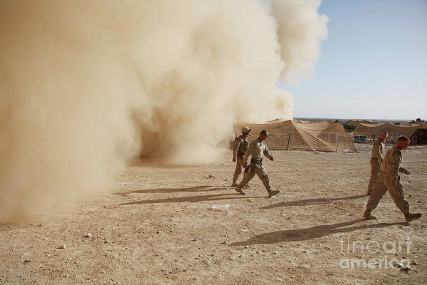 Debris Print featuring the photograph U.s. Marines Walk Away From A Dust by Stocktrek Images