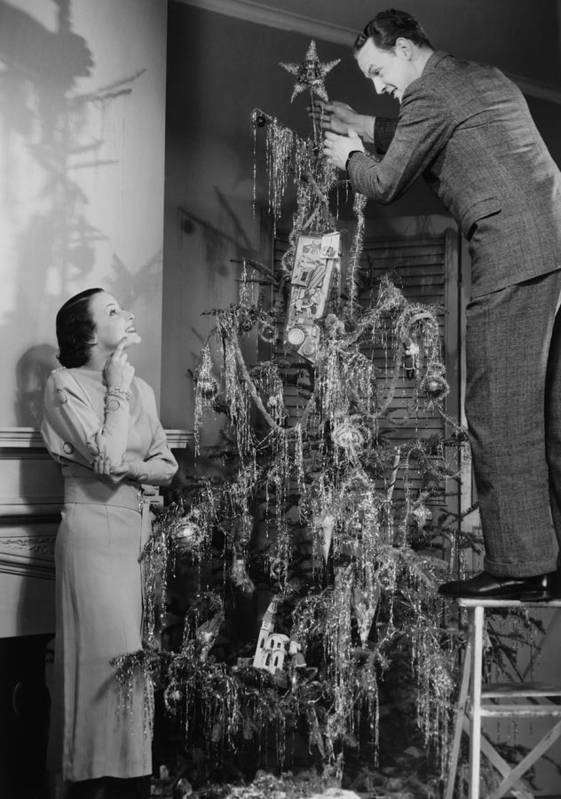 30-34 Years Print featuring the photograph Woman Assisting Man Placing Star On Top Of Christmas Tree, (b&w) by George Marks