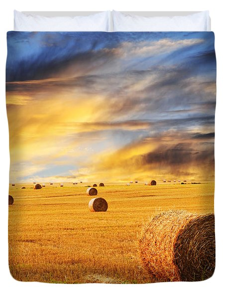 Golden sunset over farm field with hay bales Duvet Cover by Elena Elisseeva
