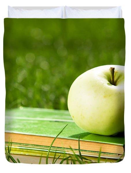 Apple on pile of books on grass Duvet Cover by Michal Bednarek