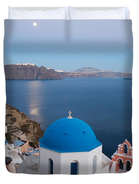 Moon over blue domed church in Oia Santorini Greece Duvet Cover by Matteo Colombo