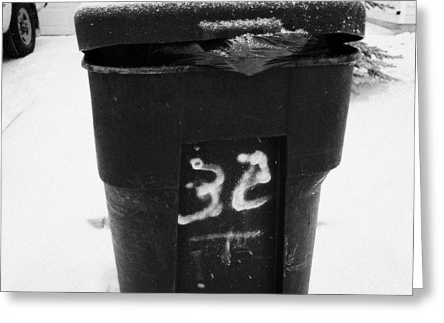 bag sticking out of litter waste bin covered in snow outside house in Saskatoon Saskatchewan Canada Greeting Card by Joe Fox