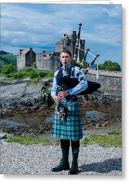 Shoreline Old Men Greeting Cards - Bagpipe player at famous Eilean Donan Castle in the highlands of Scotland Greeting Card by Frank Gaertner