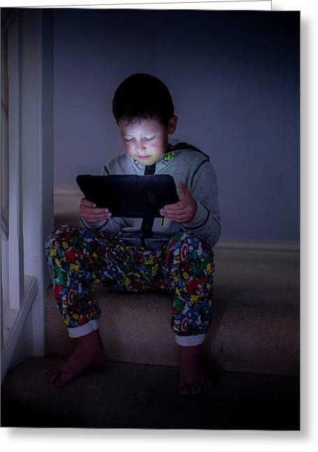 Boy Using A Digital Tablet In The Dark Greeting Card by Samuel Ashfield