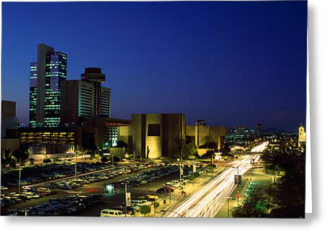 Long Street Greeting Cards - Buildings In A City Lit Up At Night Greeting Card by Panoramic Images