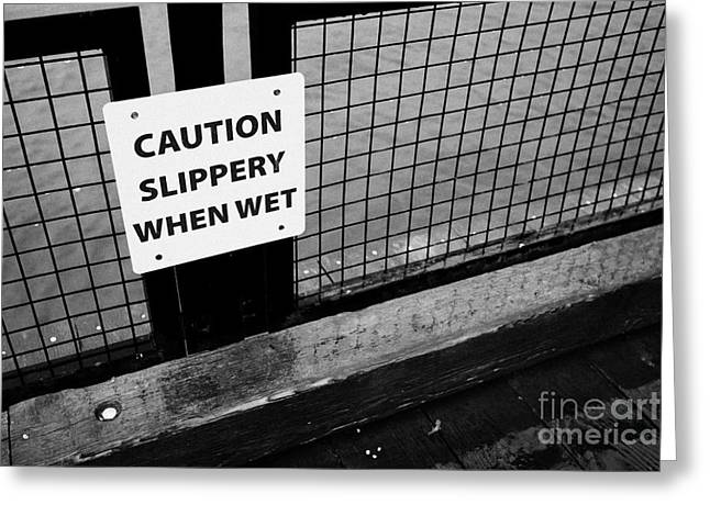 North Vancouver Greeting Cards - caution slippery when wet sign on wooden seafront walkway north Vancouver BC Canada Greeting Card by Joe Fox
