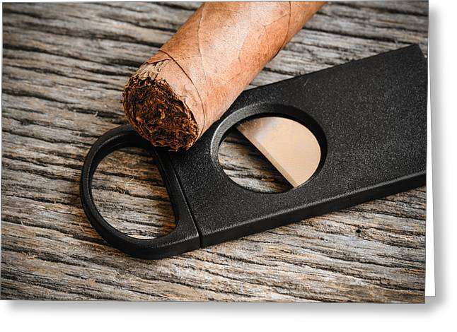 Wood Cutters Greeting Cards - Cigar and Cigar Cutter on Rustic Wood Background Greeting Card by Brandon Bourdages