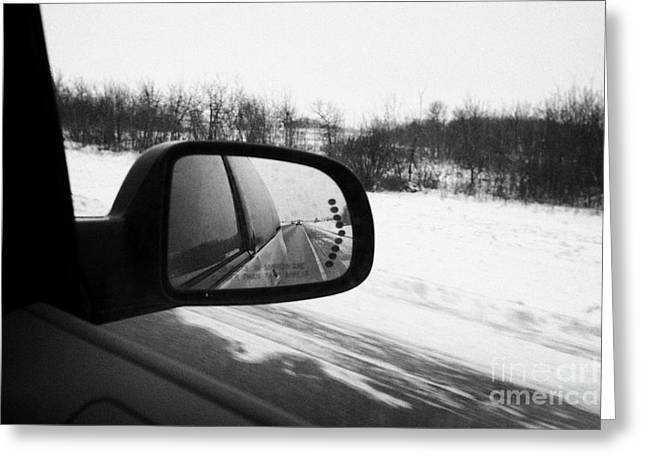 Wing Mirror Greeting Cards - looking at side view mirror winter driving along Saskatchewan highway 11 from Saskatoon to Regina Ca Greeting Card by Joe Fox