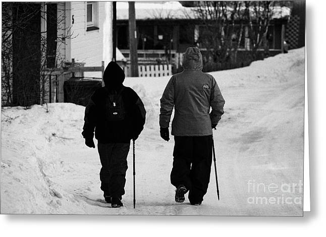 Finnmark Greeting Cards - Middle Aged Couple Walking Along Snow Covered Street With Sticks Kirkenes Finnmark Norway Europe Greeting Card by Joe Fox