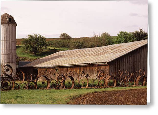 Old Barns Greeting Cards - Old Barn With A Fence Made Of Wheels Greeting Card by Panoramic Images
