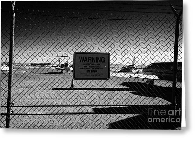 Commuter Plane Greeting Cards - security chain link fencing with warning restricted area sign on the perimeter of mccarran airport L Greeting Card by Joe Fox