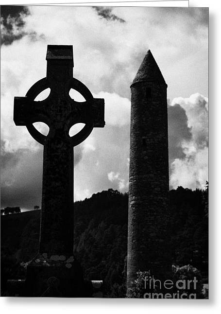 Significance Greeting Cards - St Kevins Round Tower and celtic cross headstone in graveyard at Glendalough monastic site county wicklow ireland Greeting Card by Joe Fox