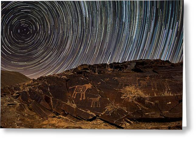 Star Valley Greeting Cards - Star trails over rock carvings Greeting Card by Science Photo Library