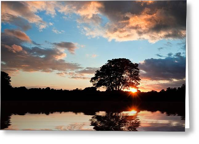 Colorful Cloud Formations Greeting Cards - Stunning sunset silhouette reflected in calm lake water Greeting Card by Matthew Gibson