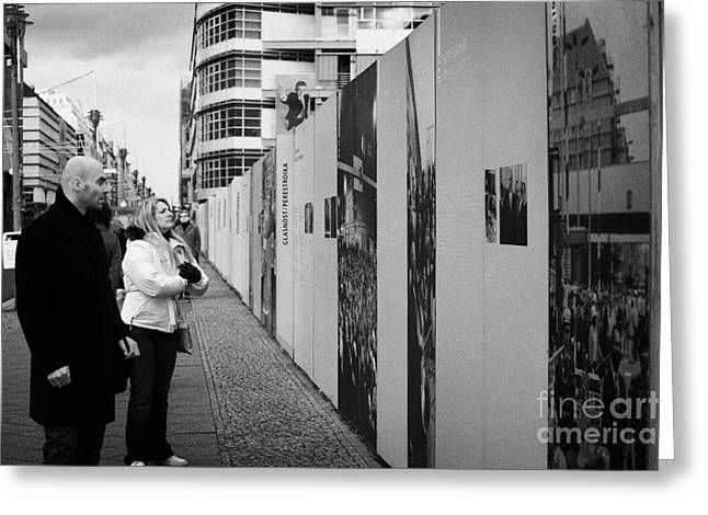 West Berlin Greeting Cards - tourists read the history of the berlin wall at checkpoint charlie Berlin Germany Greeting Card by Joe Fox