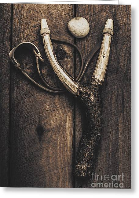 Retribution Greeting Cards - Vintage toy slingshot on wooden cubby house floor Greeting Card by Ryan Jorgensen