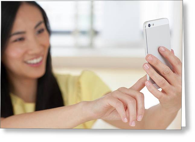 Woman Using Smartphone Greeting Card by Ian Hooton