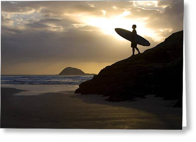 Surf Silhouette Greeting Cards - A Surfer On Muriwai Beach New Zealand Greeting Card by Deddeda